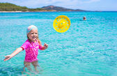 Little girl playing frisbee during tropical vacation in the sea — Zdjęcie stockowe