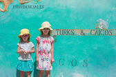 Little girls near big map of Caribbean island Turks and Caicos painted on the wall — Stock Photo
