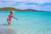 Little girl playing frisbee during tropical vacation in the sea — Stock Photo