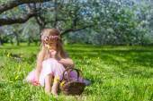 Cute little girl in blossoming apple garden at sunny spring day — Stock Photo