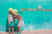 Little kids near big map of Caribbean island Turks and Caicos painted on the wall — Stock Photo