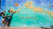 Family of four near big map of Caribbean island Turks and Caicos painted on the wall — Stock Photo