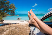 Female barefoot from the window of a car on background tropical beach — Stock Photo