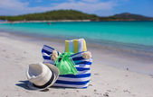Stripe bag, straw hat, sunblock and frisbee on white sandy tropical beach — Stock Photo
