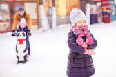 Little girl on skating rink, dad with little sister in the background — Stock Photo