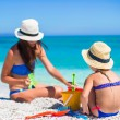 Little cute girl and young mother building sandcastle at tropical beach — Stock Photo #57508933