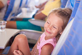 Little smiling happy girl in the aircraft — Stock Photo