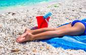 Closeup of little girl legs on tropical beach with pebbles — Stock Photo