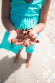 Little adorable girl with starfish in hands at the tropical beach — Stock Photo