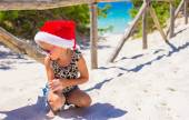 Little girl in red Santa hat on white beach outdoors — Stock Photo