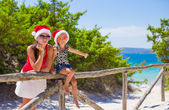 Young mother and little girl in red Christmas hat at tropical beach — Stock Photo