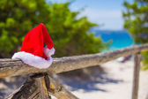 Red christmas hat on on fence background turquoise sea — Foto de Stock