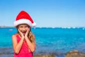 Suprised little girl in christmas hat during beach vacation — Stock Photo