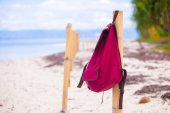Red backpack at fence on exotic tropical beach — Stock fotografie