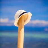 Straw hat at wooden fence on white sandy beach — Stok fotoğraf