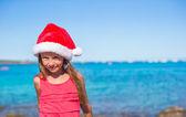 Mignonne petite fille au Bonnet de Noël sur la plage pendant les vacances — Photo