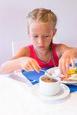 Adorable little girl having breakfast at resort restaurant — Stock Photo