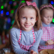 Little girls in mittens baking Christmas gingerbread cookies — Stock Photo #60184163