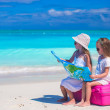 Little girls with big suitcase and map on tropical beach — Stock Photo #60187355