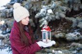 Young woman with red Christmas lantern in the snow — ストック写真