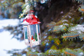 Decorative Christmas lantern on fir branch in snow winter day — Stock Photo