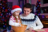 Young dad and little girl in Santa hat bake gingerbread cookies — Stock Photo