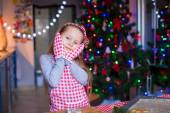 Adorable little girl in mittens baking Christmas gingerbread cookies — Stock Photo
