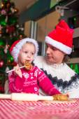 Young dad and little daughter in Santa hat bake Christmas gingerbread cookies — Stock Photo