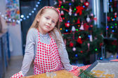 Little girl in mittens baking Christmas gingerbread cookies — Stock Photo
