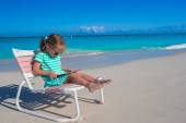 Little girl with laptop on beach during summer vacation — ストック写真