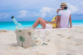 Bottle of white wine and two glasses background happy couple on sandy beach — Stockfoto