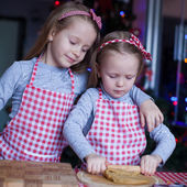 Little girls in mittens baking Christmas gingerbread cookies — Stock Photo