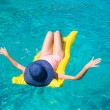 Woman relaxing on inflatable mattress in clear sea — Stock Photo #62195199