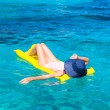 Woman relaxing on inflatable mattress in clear sea — Stock Photo #62195771