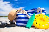 Stripe bag, straw hat, sunblock and towel on beach — Stock Photo