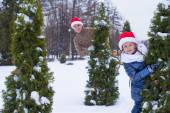 Happy father and kid in Santa hats with christmas tree outdoor — Stock Photo
