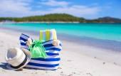 Stripe bag, straw hat, sunblock and towel on beach — Stock Photo