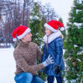 Happy father and little girl in Santa hats with christmas tree outdoor — Stock Photo