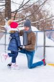 Junger Vater und liebenswert kleines Mädchen auf der Eislaufbahn im freien — Stockfoto
