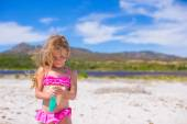Little adorable girl in swimsuit with suntan lotion bottle — Stock Photo