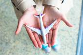 Closeup hand holding an airplane model at airport — Foto Stock