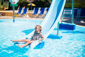 Little girl on water slide at aquapark on summer holiday — Stock Photo