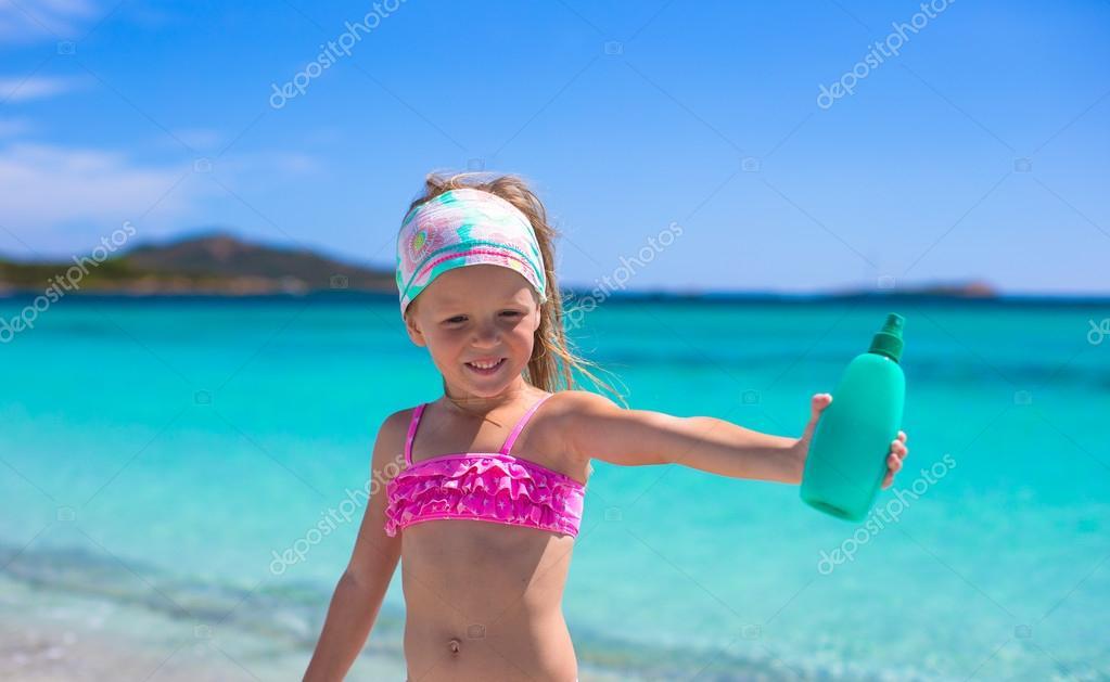 小可爱女孩的泳装,晒黑乳液瓶