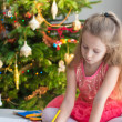 Adorable little girl drawing near Christmas tree — Stock Photo #62662313