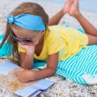 Adorable little girl with map of island on tropical beach — Stock Photo #62662669
