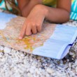 Adorable little girl with map of island on tropical beach — Stock Photo #62662913