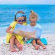 Adorable little girls with map of island on tropical beach — Stock Photo #62663289