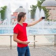 Young man using cell phone with map walking in big city — Stock Photo #62664251