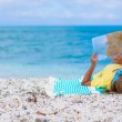 Adorable little girl with map of island on tropical beach — Stock Photo #62664585