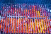 Empty black cast iron grill with hot red glowing coals — Stock Photo